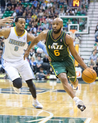 November 26, 2012; Salt Lake City, UT, USA; Utah Jazz point guard Jamaal Tinsley (6) dribbles up court while defended by Denver Nuggets shooting guard Andre Iguodala (9) during the second half at EnergySolutions Arena. The Jazz defeated the Nuggets 105-10