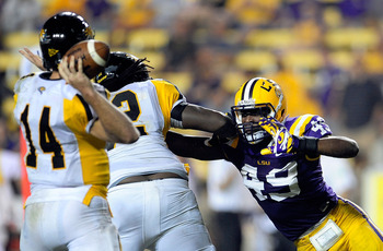 BATON ROUGE, LA - SEPTEMBER 29:  Grant Enders #14 of the Towson Tigers is pressured by Barkevious Mingo #49 of the LSU Tigers during a game at Tiger Stadium on September 29, 2012 in Baton Rouge, Louisiana.  LSU would win the game 38-22.  (Photo by Stacy R
