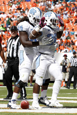 MIAMI GARDENS, FL - OCTOBER 13: Giovani Bernard #26 of the North Carolina Tar Heels is congratulated by teammate Jonathan Cooper #64 after scoring a touchdown against the Miami Hurricanes on October 13, 2012 at Sun Life Stadium in Miami Gardens, Florida.