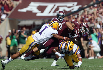 COLLEGE STATION, TX - OCTOBER 20:  Mike Evans #13 of the Texas A&M Aggies runs the ball against Eric Reid #1 and Jalen Collins #32 of the LSU Tigers at Kyle Field on October 20, 2012 in College Station, Texas.  (Photo by Ronald Martinez/Getty Images)