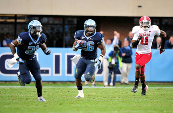 CHAPEL HILL, NC - OCTOBER 27:  Giovani Bernard #26 of the North Carolina Tar Heels breaks away from Juston Burris #11 of the North Carolina State Wolfpack to score a game-winning touchdown against the North Carolina State Wolfpack at Kenan Stadium on Octo