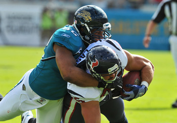 JACKSONVILLE, FL - NOVEMBER 27:  Linebacker Daryl Smith #52 of the Jacksonville Jaguars tackles fullback James Casey #86 of the Houston Texans November 27, 2011 at EverBank Field in Jacksonville, Florida. The Texans won 20 - 13. (Photo by Al Messerschmidt
