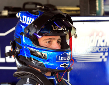 HOMESTEAD, FL - NOVEMBER 17:  Jimmie Johnson, driver of the #48 Lowe's Chevrolet, stands in the garage area during practice for the NASCAR Sprint Cup Series Ford EcoBoost 400 at Homestead-Miami Speedway on November 17, 2012 in Homestead, Florida.  (Photo
