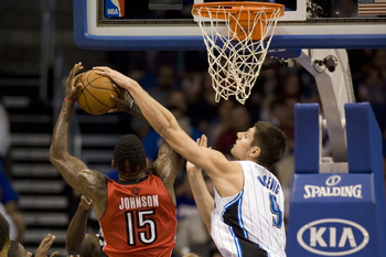 Dec 29, 2012; Orlando, FL, USA; Toronto Raptors forward-center Amir Johnson (15) is stopped at the basket by Orlando Magic center Nikola Vucevic (9) at the Amway Center. Mandatory Credit: Jeff Griffith-USA TODAY Sports