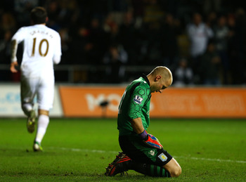 SWANSEA, WALES - JANUARY 1:   Brad Guzan, Goalkeeper of Aston Villa looks on as Danny Graham of Swansea City (L) celebrates his equalizer during the Barclays Premier League match between Swansea City and Aston Villa at the Liberty Stadium on January 1, 20