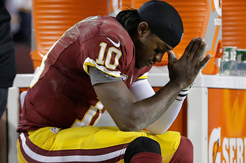 RG3 won't be the only one praying for a full recovery. (Evan Vucci/AP)