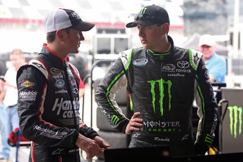 DAYTONA BEACH, FL - FEBRUARY 23:  Kurt Busch, driver of the #1 HendrickCars.com Chevrolet, (L) talks with Kyle Busch, driver of the #54 Monster Energy Toyota, in the garage during practice for the NASCAR Nationwide Series DRIVE4COPD 300 at Daytona Interna