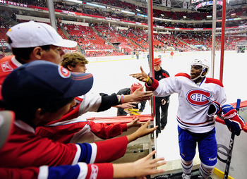 RALEIGH, NC - APRIL 05:  P.K. Subbin #76 of the Montreal Canadiens tosses a puck to the fans after warmups before a game against the Carolina Hurricanes during play at PNC Arena on April 5, 2012 in Raleigh, North Carolina.  (Photo by Grant Halverson/Getty