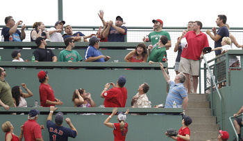 BOSTON, MA - JULY 7:  A fan in the Monster Seats tries to catch a home run ball during the first inning of game one of a doubleheader between the Boston Red Sox and the New York Yankees at Fenway Park on July 7, 2012 in Boston, Massachusetts.  (Photo by W