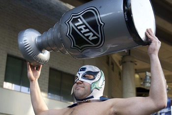 VANCOUVER, CANADA - APRIL 13: A Vancouver Canucks fan dressed as Canuck Libre hoists an inflatable Stanley Cup over his head outside Rogers Arena prior to the start of Game Two of the Western Conference Quarterfinals during the 2012 NHL Stanley Cup Playof