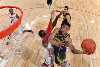 COLUMBUS, OH - JANUARY 13:  Trey Burke #3 of the Michigan Wolverines drives to the basket and shoots over Deshaun Thomas #1 of the Ohio State Buckeyes in the first half on January 13, 2013 at Value City Arena in Columbus, Ohio. Ohio State defeated Michiga