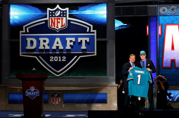 NEW YORK, NY - APRIL 26:  Ryan Tannehill from Texas A&M holds up a jersey as he stands on stage with NFL Commissioner Roger Goodell after he was selected #8 overall by the Miami Dolphins in the first round of during the 2012 NFL Draft at Radio City Music