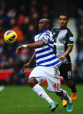 LONDON, ENGLAND - JANUARY 12:  Stephane Mbia (L) of Queens Park Rangers holds off the challenge of Kyle Naughton (R) of Tottenham Hotspur during the Barclays Premier League match between Queens Park Rangers and Tottenham Hotspur at Loftus Road on January