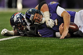Joe Flacco takes a sack in Baltimore's Week 15 loss against the Denver Broncos.