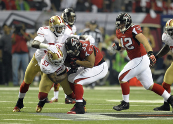 NaVorro Bowman helps bring down the Falcons' Michael Turner.