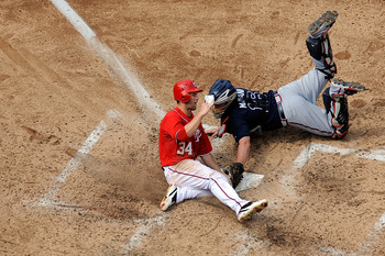 Harper and McCann meet at home plate on a close play.