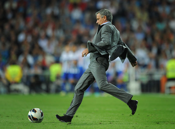 MADRID, SPAIN - SEPTEMBER 30:  Head coach Jose Mourinho of Real Madrid kicks the ball on the pitch back to his players to resume the game after conceding an early opening goal during the la Liga match between Real Madrid CF and RC Deportivo La Coruna at t