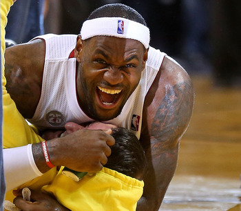 LeBron James tackles a fan with joy after the man hit a half-court shot for $75k.
