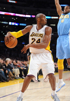 January 6, 2013;  Los Angeles, CA, USA;   Los Angeles Lakers shooting guard Kobe Bryant (24) passes the ball past Denver Nuggets shooting guard Andre Iguodala (9) in the second half of the game at the Staples Center. Nuggets won 112-105. Mandatory Credit: