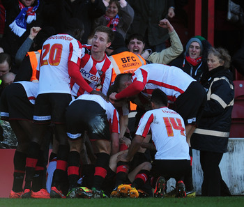 Marcello Trotta is swamped by his teammates after opening the scoring against Chelsea