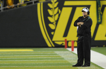 Former coach Chip Kelly standing on the Autzen Stadium sideline.