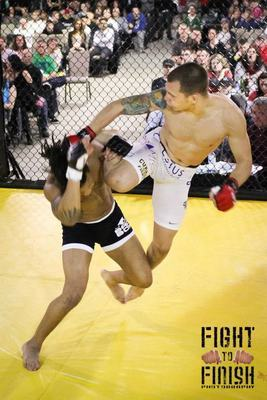 Andre Tieva [white shorts] nearly takes Ryan Sweezer's head off with a leaping head kick. (Photo thanks to Sandy Hackenmueller of Fight to Finish Photography)