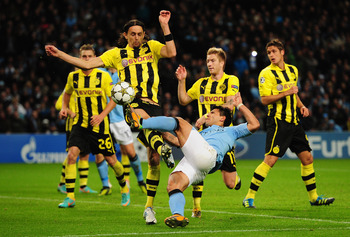 Neven Subotic challenges Manchester City striker Sergio Aguero.