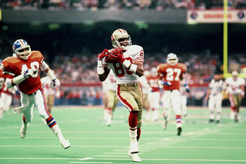 Jerry Rice brings one of three touchdowns into the end zone in the 49ers crushing blowout win over the Broncos in Super Bowl XXIV. Image via Sports Illustrated.