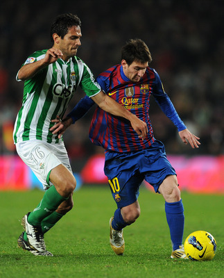 Benat Etxebarria attempts to dispossess Lionel Messi as Real Betis face FC Barcelona.