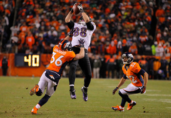 DENVER, CO - JANUARY 12:  Dennis Pitta #88 of the Baltimore Ravens makes a first down reception in overtime against Jim Leonhard #36 and Tony Carter #32 of the Denver Broncos during the AFC Divisional Playoff Game at Sports Authority Field at Mile High on