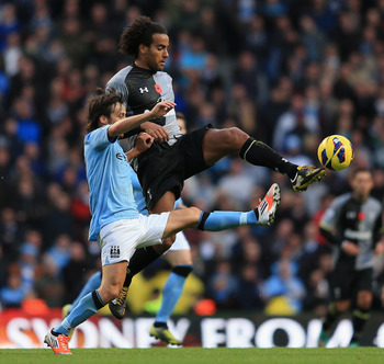 Tom Huddlestone gets a toe in front of Manchester City's David Silva.
