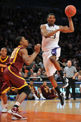 NEW YORK, NY - MARCH 27: C.J. Wilcox  #23 of the Washington Huskies looks to pass the ball past Andre Ingram #30 of the Minnesota Golden Golphers in the first half during the semifinals of the NIT men's basketball championship at Madison Square Garden on