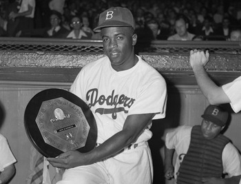Jackie Robinson displays his NL MVP award for the 1949 season (image courtesy of www.biography.com).