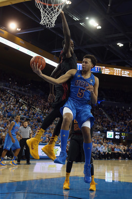 LOS ANGELES, CA - JANUARY 30:  Kyle Anderson #5 of the UCLA Bruins passes the ball off while defended by Dewayne Dedmon #14 of the USC Trojans in the second half at Pauley Pavilion on January 30, 2013 in Los Angeles, California. USC defeated UCLA 75-71 in