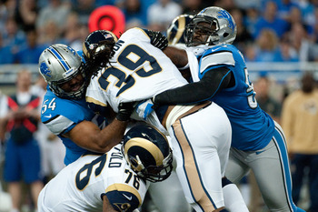 Levy (54) and Durant wrap up the Rams' Steven Jackson.