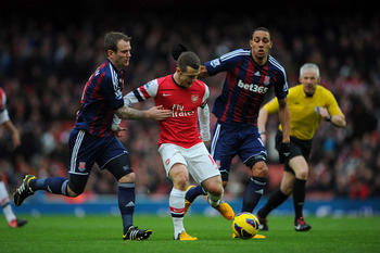Jack Wilshere bursts between two Stoke midfielders.