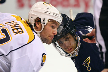 Nashville Predator Mike Fisher and St. Louis Blue Andy McDonald take a faceoff.