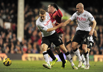 LONDON, ENGLAND - FEBRUARY 02:  Wayne Rooney of Manchester United runs into Brede Hangeland of Fulham during the Barclays Premier League match between Fulham and Manchester United at Craven Cottage on February 2, 2013 in London, England.  (Photo by Jamie