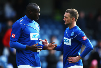 LONDON, ENGLAND - FEBRUARY 02:  Christopher Samba of Queens Park Rangers talks to his team- mate Clint Hill in the warm up prior to the Barclays Premier League match between Queens Park Rangers and Norwich City at Loftus Road on February 2, 2013 in London