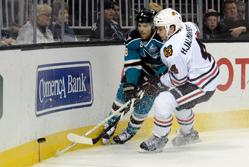 Joe Pavelski battles along the boards with Niklas Hjalmarsson.