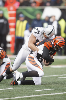 CINCINNATI, OH - NOVEMBER 25:  Matt Shaughnessy #77 of the Oakland Raiders sacks Andy Dalton #14 of the Cincinnati Bengals during their game at Paul Brown Stadium on November 25, 2012 in Cincinnati, Ohio.  The Bengals defeated the Bengals 34-10.  (Photo b