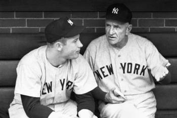 Manager Casey Stengel talks with Mickey Mantle before a 1953 game at Comiskey Park in Chicago. (Photo by Robert Lerner/Getty Images)
