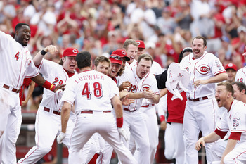 CINCINNATI, OH - JULY 14: Ryan Ludwick #48 of the Cincinnati Reds celebrates with teammates at home plate after hitting the game-winning home run in the tenth inning against the St. Louis Cardinals at Great American Ball Park on July 14, 2012 in Cincinnat