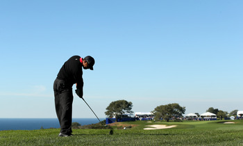 Tiger Woods tees off with the Pacific Ocean in the distance.