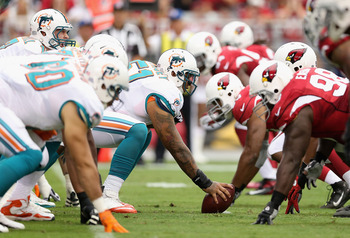 GLENDALE, AZ - SEPTEMBER 30:  Center Mike Pouncey #51 of the Miami Dolphins prepares to snap the football to quarterback Ryan Tannehill #17 during the NFL game against the Arizona Cardinals at the University of Phoenix Stadium on September 30, 2012 in Gle