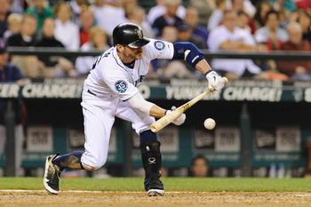 Aug 18, 2012; Seattle, WA, USA; Seattle Mariners shortstop Brendan Ryan (26) hits a bunt single against the Minnesota Twins during the 9th inning at Safeco Field. Mandatory Credit: Steven Bisig-USA TODAY Sports
