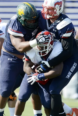 Jan 23, 2013;  Mobile AL, USA; Senior Bowl north squad defensive lineman Brandon Williams of Missouri Southern (66) and defensive lineman Margus Hunt of SMU (96) wrap up running back Robbie Rouse of Fresno State (28) during the Senior Bowl north squad pra