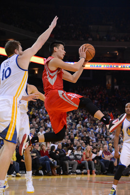 February 12, 2013; Oakland, CA, USA; Houston Rockets point guard Jeremy Lin (7, right) passes the ball against Golden State Warriors power forward David Lee (10) during the first quarter at Oracle Arena. Mandatory Credit: Kyle Terada-USA TODAY Sports