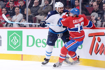 Dustin Byfuglien, Winnipeg Jets, introduces himself to Brendan Gallagher of the Montreal Canadiens. Girl in the front row has loved Gallagher all all along and now fears Big Buff's interference. Speaking of which, where is the puck?