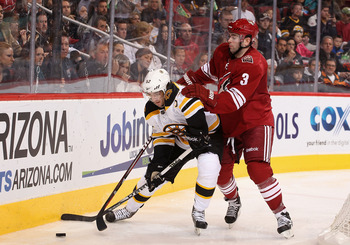 Keith Yandle of the Phoenix Coyotes informs a member of the Boston Bruins that he actually (believe it or not) grew up in &quot;Titletown&quot; and would like to be an honorary member.